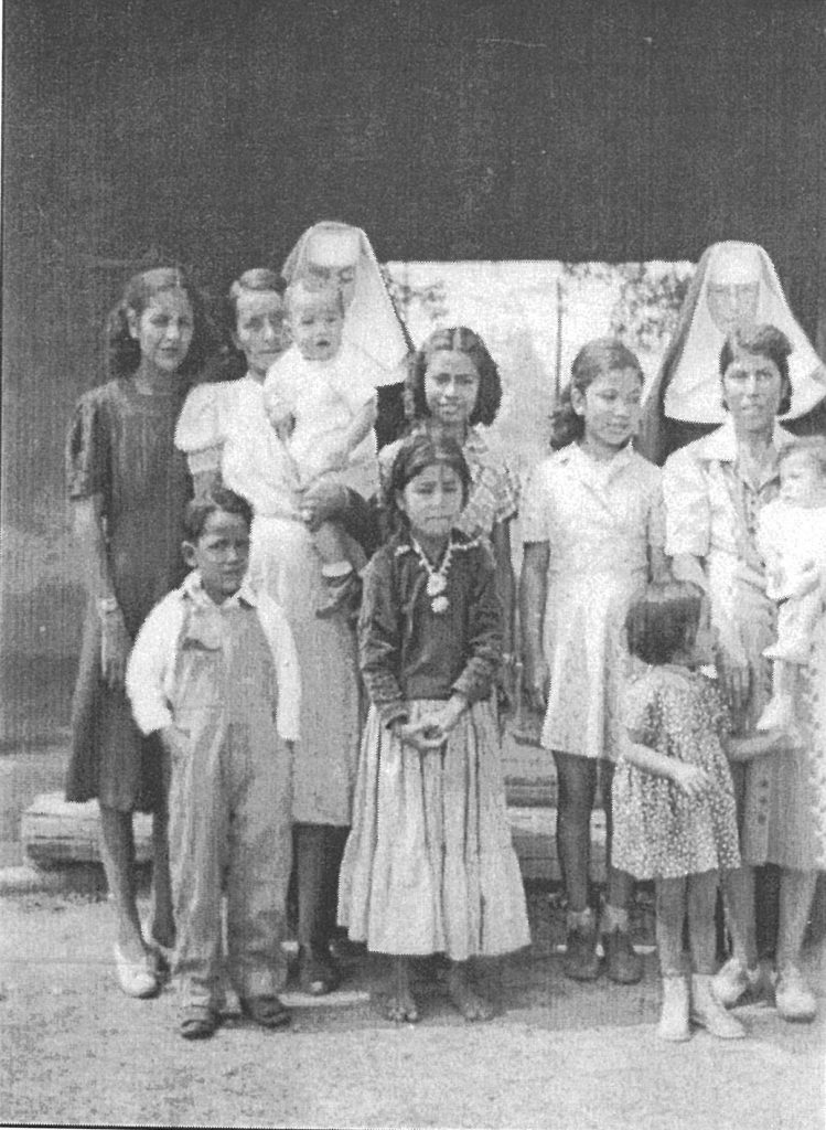 """This was taken at the """"section house"""" in Pinta. It shows Sr. Francis on the right in the back. In front of her is Loretto Tso. The Navajo girl in the front is Nellie Yazzie Shirley and in back of her is Stennie Ashley."""