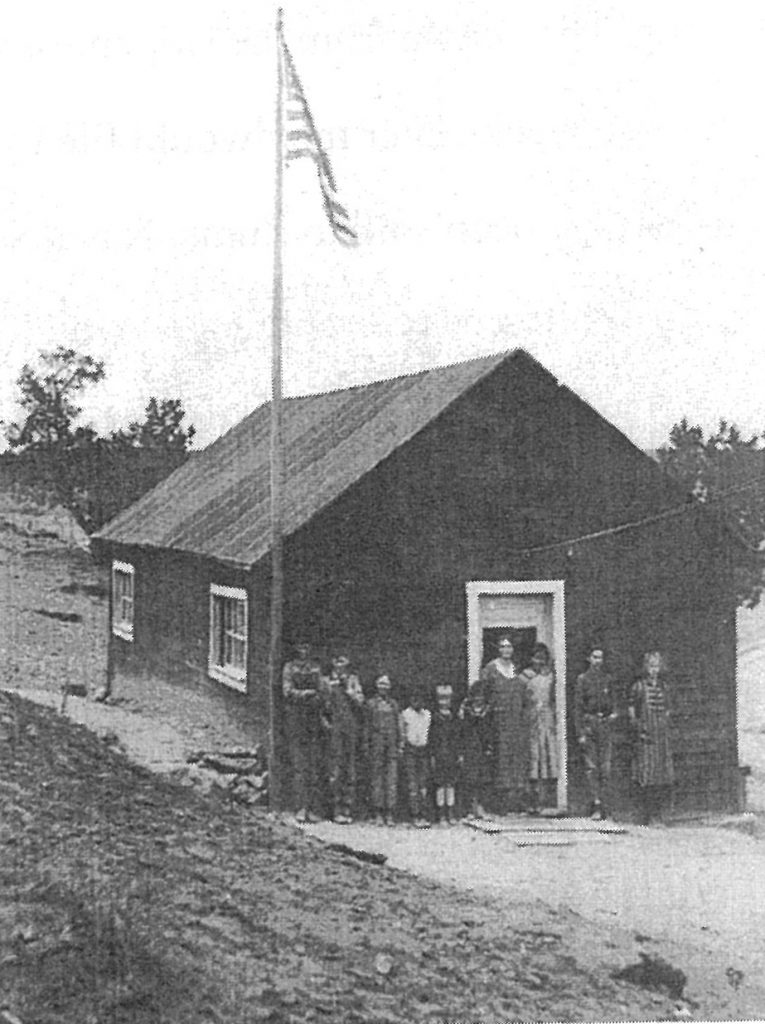 This is the first schoolhouse in Houck. It stood southwest of the mission across the puerco wash near some windmills. The boy fourth from the left (in the white shirt) is Henry Morgan.