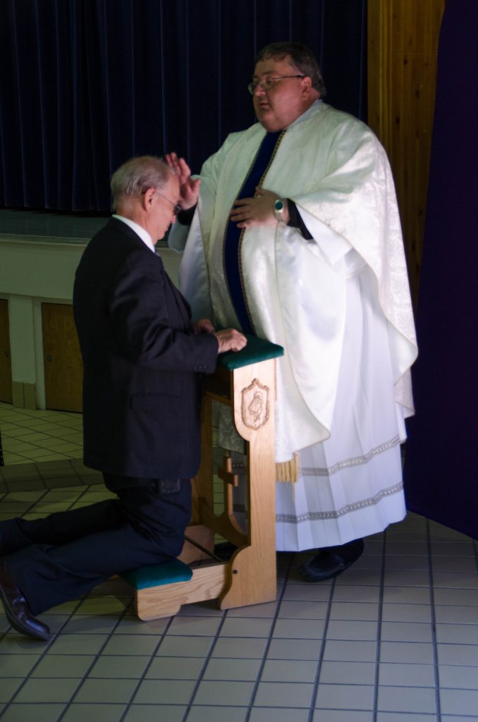 Fr. Badger gives a blessing to his father.