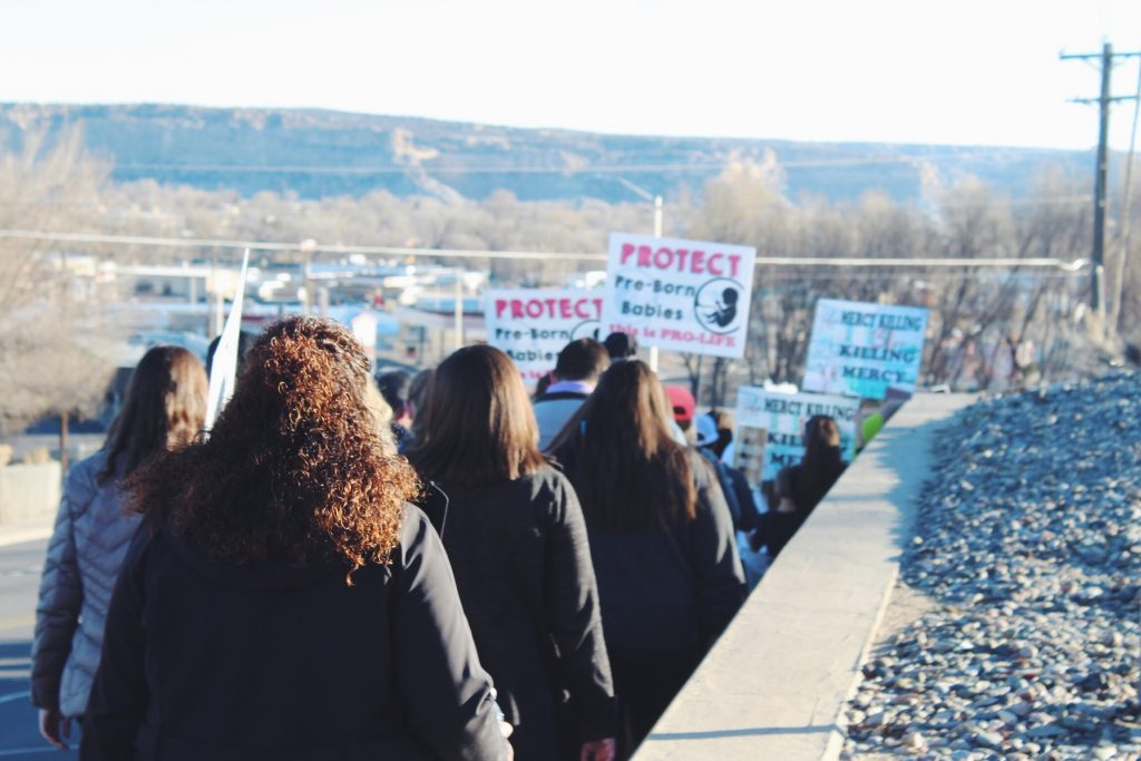 Demonstrators hold signs during the 2018 Farmington Walk for Life.